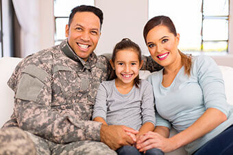 military family, husband in uniform with wife and daughter smiling while sitting on couch